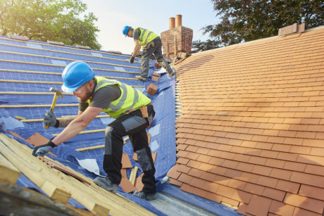 Construction workers laying roof tiles that contain boron